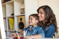 Young woman with little girl using computer at home